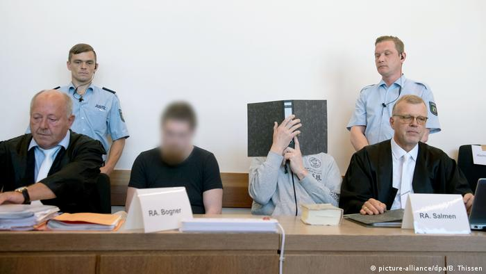 Two of the accused in court, one of them hiding his face (picture-alliance/dpa/B. Thissen)
