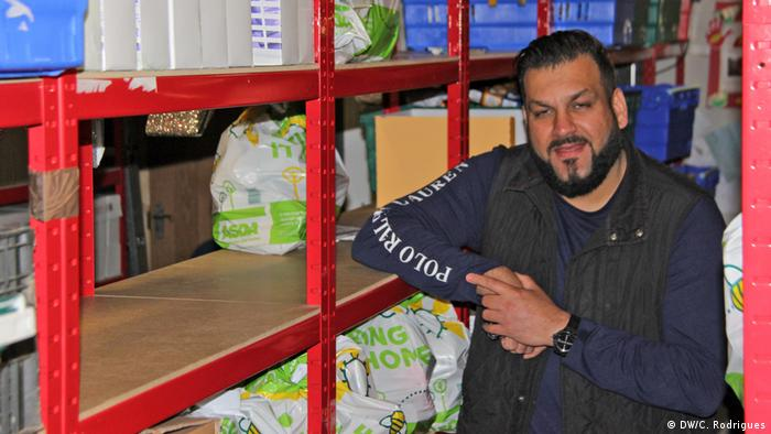 The owner of a food bank sitting next to his goods