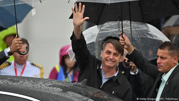 Brazilian President Jair Bolsonaro waves as he arrives at Kansai airport in Izumisano city, Osaka prefecture, on June 27, 2019 ahead of the G20 Osaka Summit.
