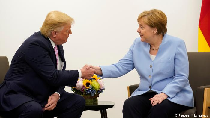 US President Donald Trump shakes hands with Germany's Chancellor Angela Merkel during a bilateral meeting at the G20 leaders summit in Osaka (Reuters/K. Lamarque)