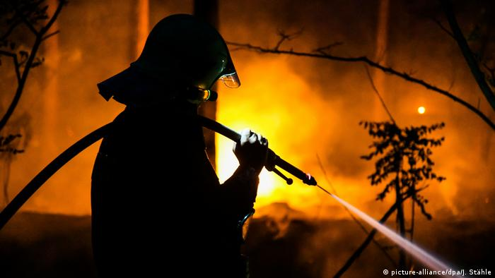 A firefighter holds a hose with water spraying out of it