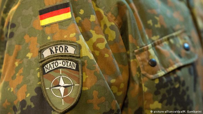 A Bundeswehr uniform shows the NATO KFOR mission patch underneath the German tri-color flag