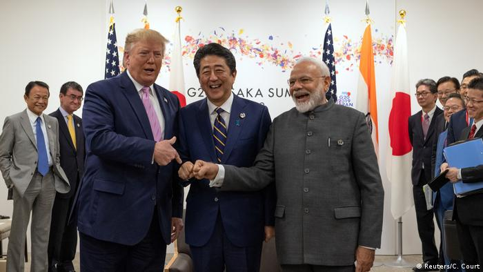 U.S. President Donald Trump jokes to the media about fist bumping with Japan's Prime Minister Shinzo Abe and India's Prime Minister Narendra Modi (Reuters/C. Court)