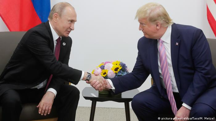 Russian President Vladimir Putin and US President Donald Trump shake hands at the G20 meeting in Osaka, Japan