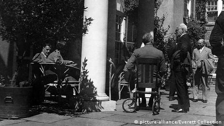 Franklin D. Roosevelt sitzt in einem Rollstuhl vor dem Weißen Haus