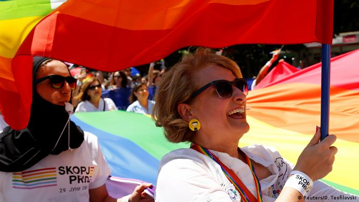 Woman holds up a rainbow flag at Skopje Pride Parade