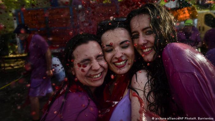 Revelers smile while taking part in a wine battle, in the small village of Haro, northern Spain.