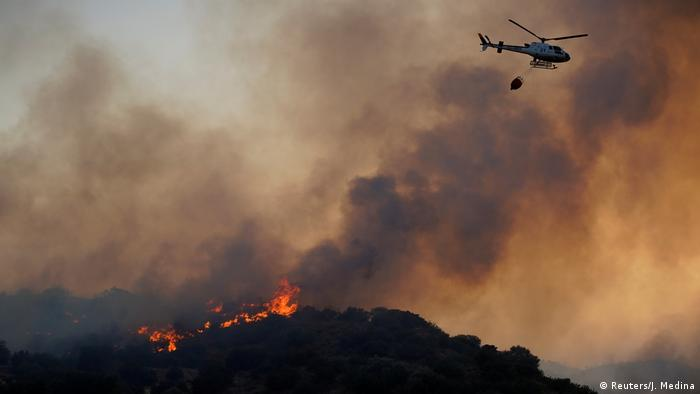 A helicopter flies over a wildfire near the city of Toledo, Spain