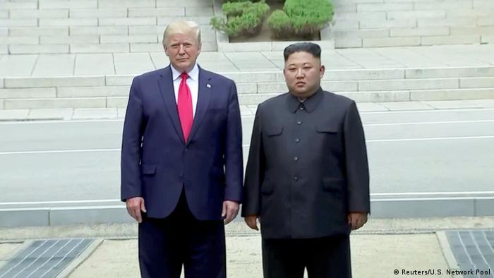 Donald Trump stands next to Kim Jong Un
