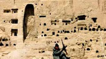An armed Afghan man stands guard as the location of the destroyed Buddha statue, left, is seen behind him in Bamiyan, central Afghanistan, Tuesday April 9, 2002.