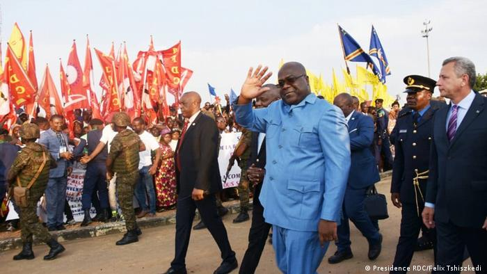 President Tshisekedi waves as his delegation pass a crowd of supporters