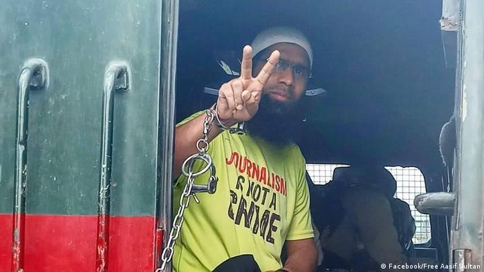 Man wearing 'Journalism is not a crime' holds up his fingers in the peace sign