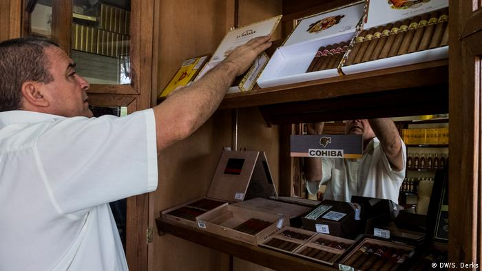 A man stacking goods in a cigar shop