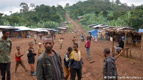 People stand on a dirt road with market stalls and houses along the sides