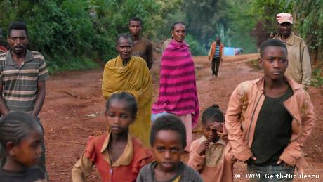 Men, women and children stand on a dirt road