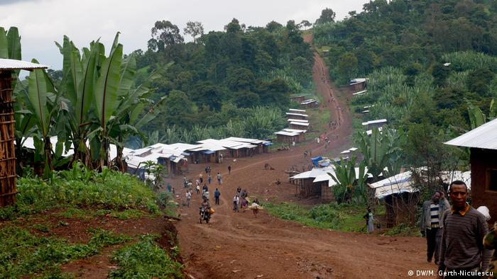 A dirt road runs through a village lines with huts