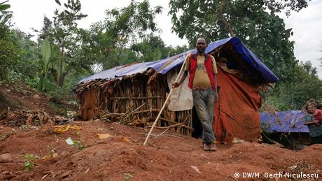 A man stands in front of a temporary shelter built with banana leaves, sticks and plastic