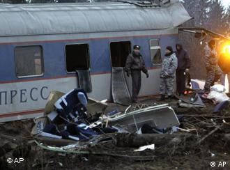Russian police officers inspect a damaged coach at the site of a train derailment near the town of Uglovka