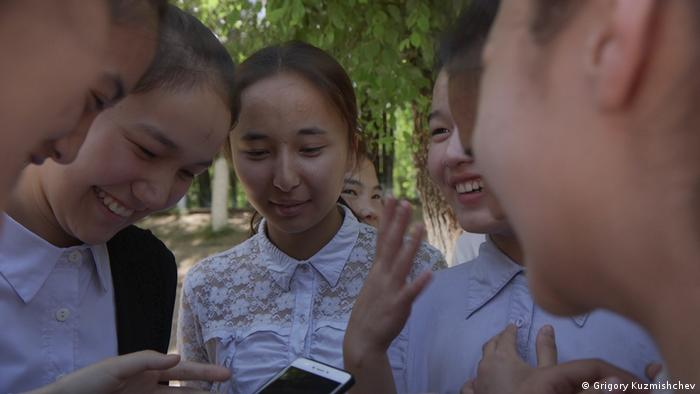 Students at the village school in Kainazar chat on their mobile phones (Photo: Grigory Kuzmishchev)