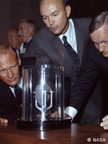 Astronauts Buzz Aldrin, Michael Collins and Neil Armstrong view one of their lunar rock samples after their return (NASA)
