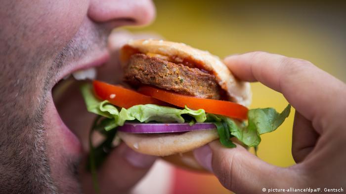 Un hombre comiendo una hamburguesa