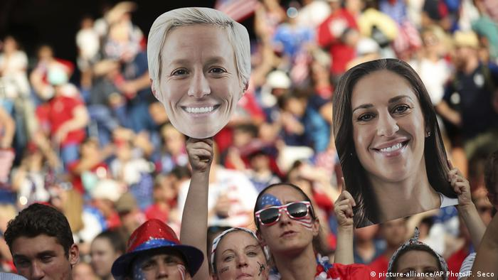 Fans holding up images of US women's national football team players