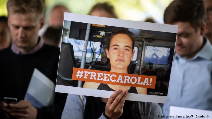 A person displays a sign saying #FreeCarola