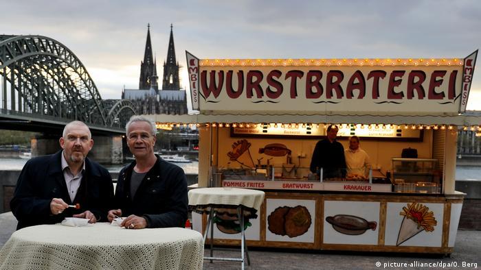 Die Wurstbraterei der Kölner Tatort-Kommissare vor dem Rhein mit Blick auf den Kölner Dom und die Hohenzollernbrücke. Im Vordergrund die Tatort-Kommissare Ballauf und Schenk (picture-alliance/dpa/O. Berg)