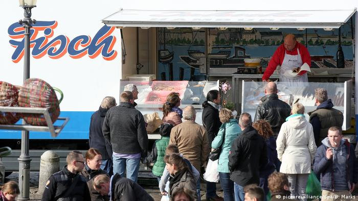 people line up for fish sandwiches at a stall (picture-alliance/dpa/B. Marks)