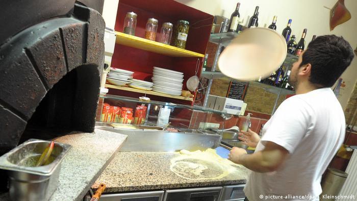 Ein Pizzabäcker neben dem Steinofen wirft den Teig in die Luft (picture-alliance/dpa/T. Kleinschmidt)