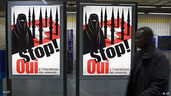 A man walks past a controversial Swiss political poster, which depicts a fully veiled Muslim women wearing black. Behind her, a number of black minarets stand on, and obstruct the Swiss flag. Prominently printed in the foreground are the French language words meaning stop and yes.