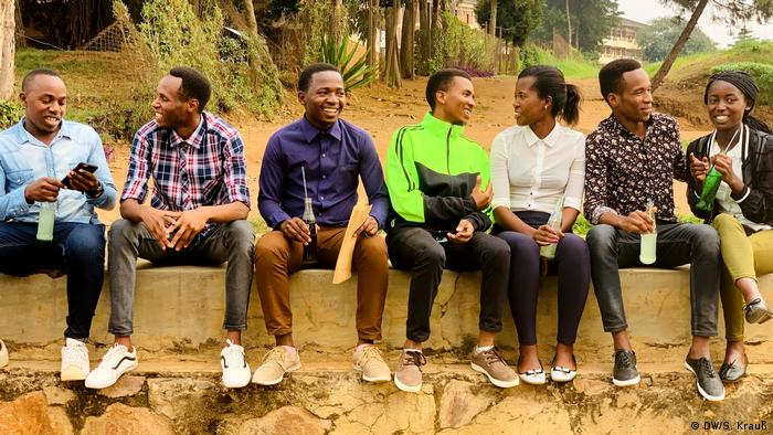 A group of young Rwandans sitting on a wall and chatting (DW. S. Krauß)