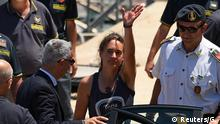 FILE PHOTO: Carola Rackete, the 31-year-old Sea-Watch 3 captain, disembarks from a Finance police boat and is escorted to a car, in Porto Empedocle, Italy July 1, 2019. REUTERS/Guglielmo Mangiapane/File Photo