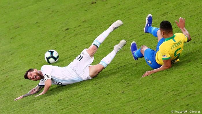 À esquerda, Lionel Messi grita após queda em jogada com Casemiro, que também cai sentado no gramado e deixa a bola rolando ao fundo na partida que eliminou a Argentina na semifinal da Copa América.