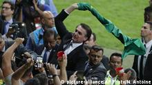 Brazil's President Jair Bolsonaro waves a national flag during a Copa America semifinal soccer match against Argentina at the Mineirao stadium in Belo Horizonte, Brazil, Tuesday, July 2, 2019. (AP Photo/Nelson Antoine) |
