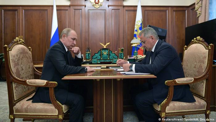 Russia's President Vladimir Putin and Defence Minister Sergei Shoigu sit accross from each other at a desk at the Kremlin during a meeting to discuss a recent incident with a Russian deep-sea submersible