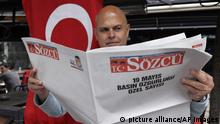 """A Turkish man poses with a copy of the opposition Sozcu newspaper, a staunch supporter of the legacy of Turkey's founder Mustafa Kemal Ataturk and a vocal critic of Turkey's president Recep Tayyip Erdogan, in Ankara, Turkey, Saturday, May 20, 2017. A Turkish opposition paper has published its Saturday edition left blank in protest of detentions. Nationalist Sozcu newspaper titled its publication """"May 19 Press Freedom Special Edition."""" It carried empty columns with writers' names and also left the weather blank. (AP Photo/Burhan Ozbilici) 