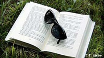Buch mit Sonnenbrille im Gras