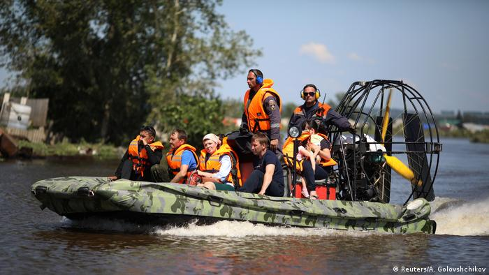 Mitarbeiter des Katastrophenschutzes evakuieren Flutopfer