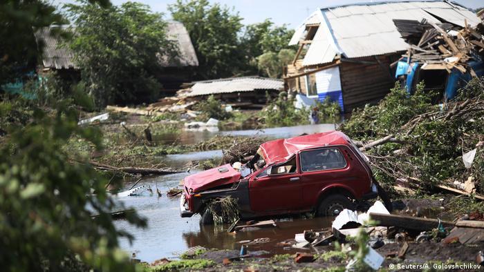 Beschädigtes Auto vor einem zerstörten Haus.