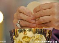 Sacerdote parte la hostia durante la Eucaristía.