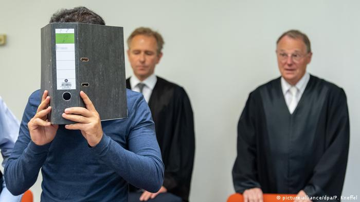 An Afgan man blocking his face with a binder faces war crimes charges at a Munich court