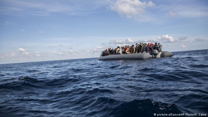 Asylum-seekers sit in a rubber dinghy awaiting rescue in the Mediterranean Sea