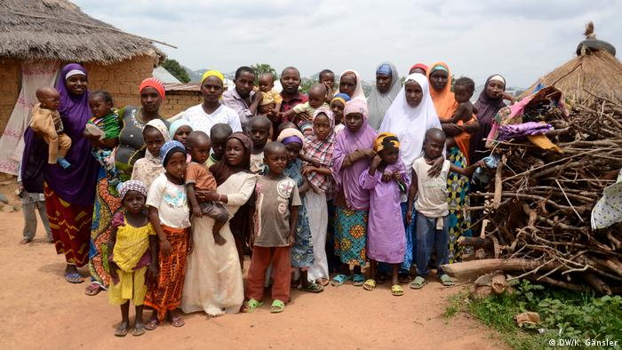Men, women and children pose for a picture in the village