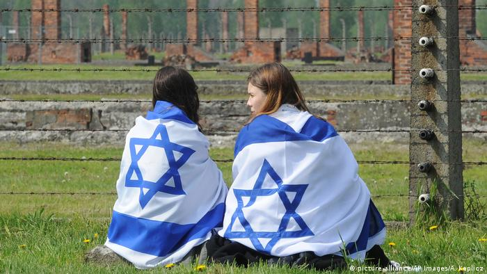 Two young women draped in Israeli flags in Auschwitz
