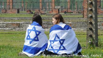 Девушки с флагами Израиля сидят перед колючей проволокой