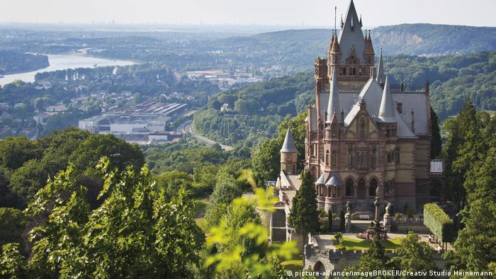 Small castle overlooking a verdant valley with a river snaking in the background (picture-alliance/imageBROKER/Creativ Studio Heinemann)