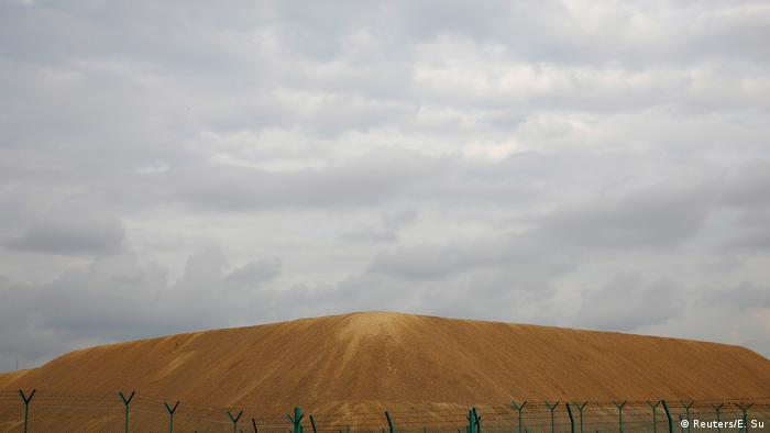 A mound of golden sand behind a barbed wire fence in Singapore
