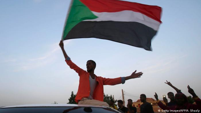 A man waves the Sudanese flag from atop a car (Getty Images/AFP/A. Shazly)