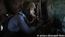 Ukrainian President Volodymyr Zelenskiy looks at the front line position from a shelter as he visits the war-hit Luhansk region, eastern Ukraine, Monday, May 27, 2019. (Ukrainian Presidential Press Office via AP) |